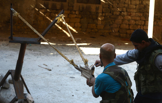 Syrian rebels prepare to launch a bomb using a homemade slingshot in the northern city of Aleppo, on October 16, 2012. Lightly-armed Syrian rebels who face the warplanes, artillery and tanks of loyalists have turned to making their own weapons, even rigging a video game controller to fire mortar rounds. (Photo by Tauseef Mustafa/AFP Photo)
