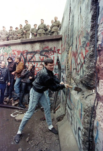 A demonstrator pounds away at the Berlin Wall as East Berlin border guards look on from above the Brandenburg Gate in Berlin in this November 11, 1989 file photo. (Photo by David Brauchli/Reuters)