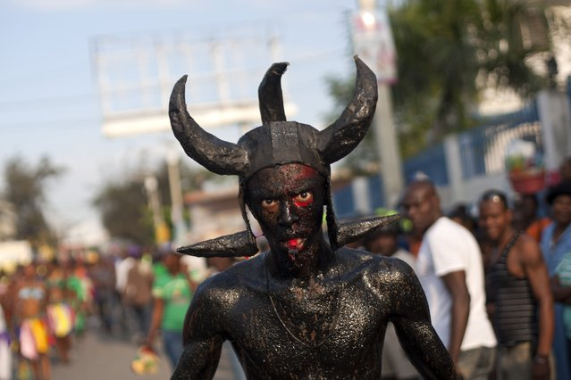 A man, decked out with horns and his body smothered in clay mud and oil, marches in a Carnival parade to the national palace, in Port-au-Prince, Haiti, Monday, February 16, 2015. (Photo by Dieu Nalio Chery/AP Photo)