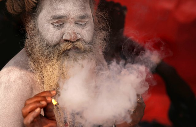 An Indian monk enjoys holy smoke at a transit camp as pilgrims arrive for the upcoming Gangasagar Fair at Sagar Island, in Calcutta, eastern India, 05 January 2016. The Gangasagar Fair is an annual gathering of Hindu pilgrims during Makar Sankranti at Sagar Island, 130 km south of Calcutta in West Bengal, to take a dip in sacred waters of Ganga River before she merges in the Bay of Bengal. (Photo by Piyal Adhikary/EPA)