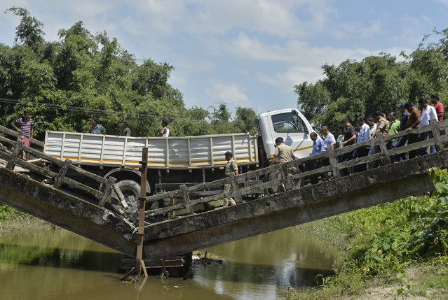 Indian rescue workers and villagers gather near a collapsed bridge in Phasidewa village near the India-Bangladesh border on the outskirts of Siliguri in the Indian state of West Bengal on September 7, 2018. No casualties were reported in the collapse. (Photo by Diptendu Dutta/AFP Photo)