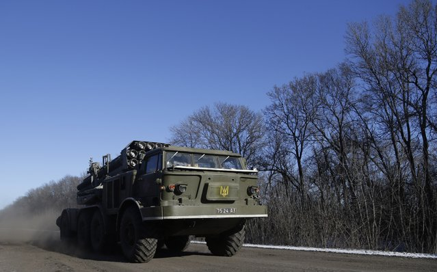 A Ukrainian army's truck with a Smerch missile launcher passes on a road stretching away from the town of Artemivsk, Ukraine, towards Debaltseve, Tuesday, February 17, 2015. (Photo by Petr David Josek/AP Photo)