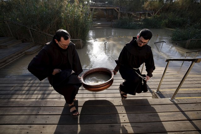 Christians carry a basin containing water during a ceremony at the baptismal site known as Qasr el-Yahud on the banks of the Jordan River near the West Bank city of Jericho, January 10, 2016. It is believed that John the Baptist baptised Jesus in this site. (Photo by Mohamad Torokman/Reuters)