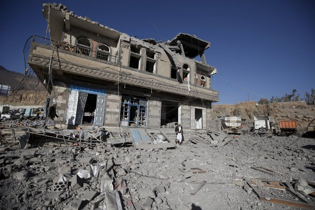 People walk next to a damaged building at the site of a Saudi-led air strike in Yemen's capital Sanaa January 4, 2016. (Photo by Khaled Abdullah/Reuters)