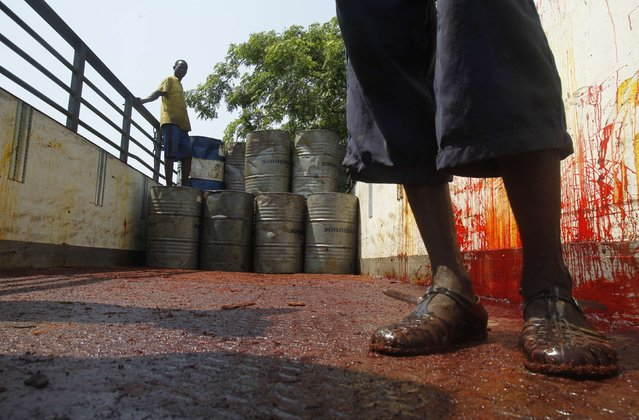 Men unload oil barrels from a truck at a traditional soap factory in Adjame, an area of Abidjan, on February 13, 2015. (Photo by Luc Gnago/Reuters)