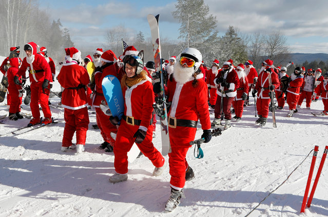 Skiers and snowboarders dressed as Santa prepare to board the ski lift as they participate in a charity run down a slope at Sunday River Ski Resort in Newry, Maine, U.S. December 4, 2016. (Photo by Joel Page/Reuters)