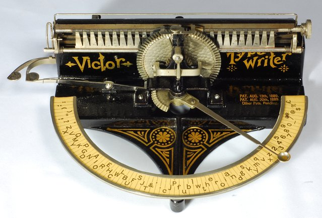 Victor index. Tilton Mfg. Co., Boston, 1889. The Victor is a beautiful Victorian typewriter with handsome decals. This was the first typewriter to use a daisy wheel, which would be a common design feature on 1980s typewriters. The daisy wheel is made of thin brass, cut with narrow radial fingers, one for each character. At the end of each finger is an embossed rubber character. To operate the Victor one puts the tip of ones index finger in the little cup at the end of the pointer, then swings the pointer up to a full 180 degrees to select the characters. The pointer is connected by a gear to the central vertical wheel that holds the daisy wheel. As the pointer swings, the daisy wheel rotates into position. A spring-loaded hammer then pushes the brass finger in the daisy wheel against the paper. This typewriter originally sold for $15.00. (Photo and caption by Martin Howard/Martin Howard Collection)