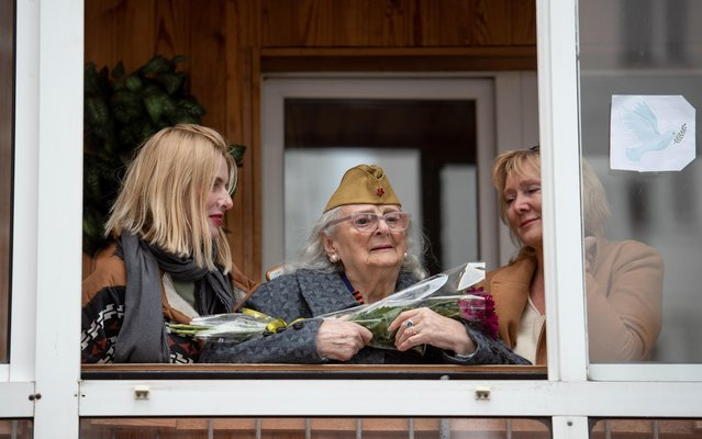 """World War Two veteran Valentina Startseva, 96, accompanied by her daughter and granddaughter, watches a concert out of her balcony as she receives congratulations from members of the military-historical society """"Krepost"""" (Fortress) on the upcoming Victory Day, which marks the anniversary of the victory over Nazi Germany, in Tomsk, Russia on May 4, 2021. (Photo by Taisiya Vorontsova/Reuters)"""