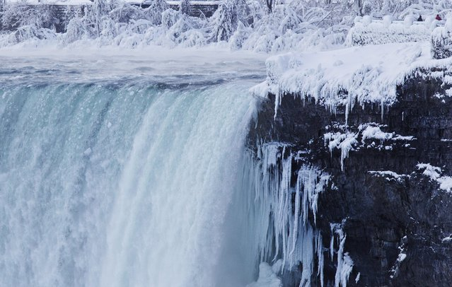 "Visitors look over masses of ice formed around the Canadian ""Horseshoe"" Falls in Niagara Falls, Ontario, Canada, Thursday, February 19, 2015. (Photo by Aaron Lynett/AP Photo/The Canadian Press)"