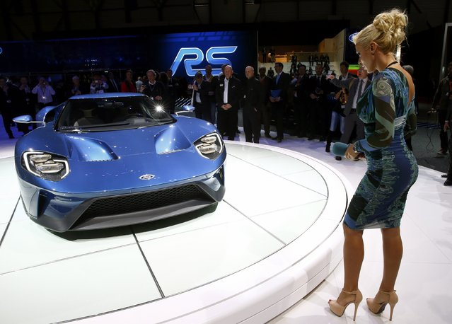 A TV presenter looks at a Ford GT during the first press day ahead of the 85th International Motor Show in Geneva March 3, 2015. REUTERS/Arnd Wiegmann