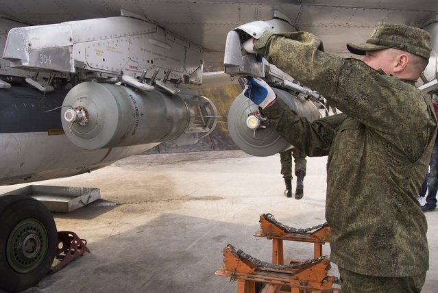 A Russian air force technician attaches a bomb to a Russian ground attack jet at Hemeimeem air base in Syria on Wednesday, January 20, 2016. (Photo by Vladimir Isachenkov/AP Photo)