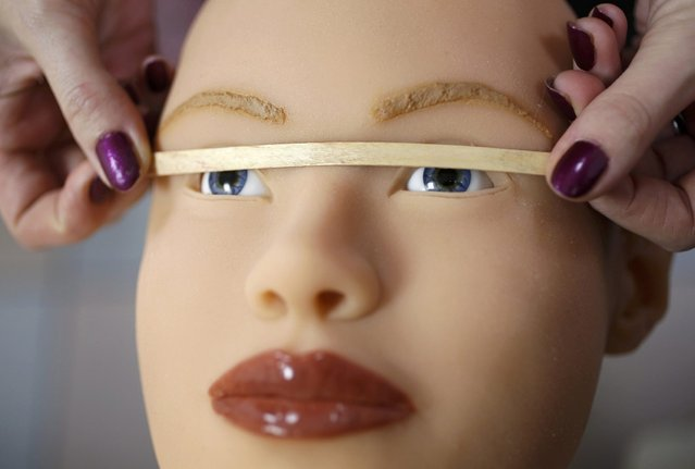 Raphaela, an employee at the Dreamdoll company, checks eye alignment on a silicone dream doll in their workshop in Duppigheim near Strasbourg, December 2, 2014. The realistic silicone s*x dolls can be ordered from a catalogue based on four hair and eye color models for a base price of 5,500 euros ($6,150). (Photo by Vincent Kessler/Reuters)