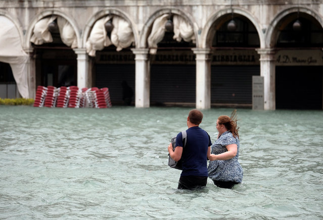 A couple walk in the flooded Saint Mark Square during a period of seasonal high water in Venice, Italy October 29, 2018. (Photo by Manuel Silvestri/Reuters)