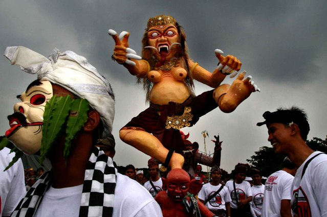"Indonesian Hindu devotees carry giant ""Ogoh-ogoh"" effigies symbolising evil during a procession before they are burned in a ritual to purify worshippers from evil in Malang, eastern Java island on March 20, 2015 on the eve of Nyepi, the Hindu new year. In the nearby island of Bali, tourists and residents totally stay indoors for a day of reflection, free from daily routine including work and play in the entire island of Bali as Indonesia's minority Hindu population marks Nyepi day in full solemnity. (Photo by Aman Rochman/AFP Photo)"