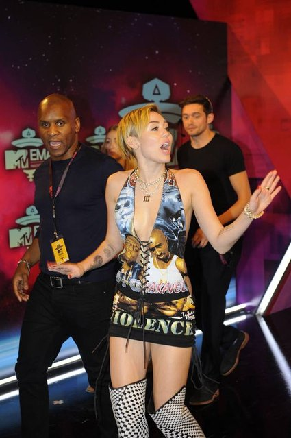 US singer and actress Miley Cyrus (C) gestures as she arrives to attend the MTV European Music Awards (EMA) 2013 at the Ziggo Dome on November 10, 2013 in Amsterdam, The Netherlands. (Photo by John Thys/AFP Photo)