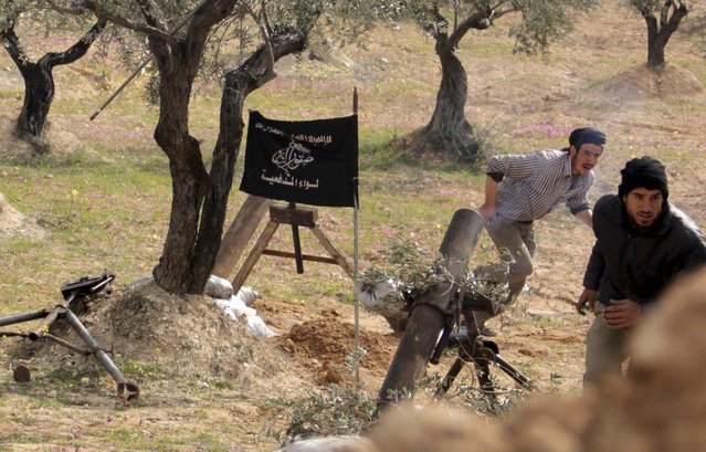 Rebel fighters from Suqour al-Sham Brigade run for cover during the launching of mortar shells towards forces loyal to Syria's president Bashar Al-Assad in Idlib countryside March 19, 2015. (Photo by Mohamad Bayoush/Reuters)