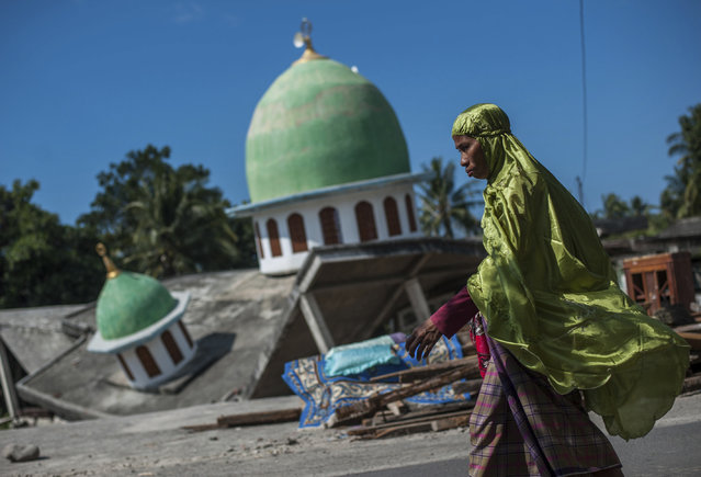 In this Saturday, August 11, 2018, photo, a Muslim woman walks past a mosque collapsed during Sunday's earthquake in Gangga, Lombok Island, Indonesia. Scientists say the powerful earthquake that killed hundreds of people lifted the island it struck by as much as 25 centimeters (10 inches). (Photo by Fauzy Chaniago/AP Photo)