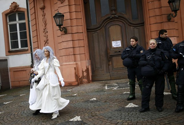 """Police patrol as revellers take part in the traditional """"Weiberfastnacht"""" (Women's Carnival) celebration in Mainz, Germany, February 4, 2016. Germany is celebrating its traditional carnival with tight security after assaults on women during New Year's Eve celebrations across the country. (Photo by Kai Pfaffenbach/Reuters)"""