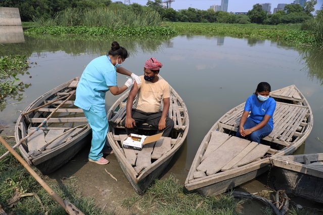 A health worker administers a vaccine for COVID-19 to a boatman on an island in the River Yamuna in New Delhi, India, Friday, July 16, 2021. (Photo by Amit Sharma/AP Photo)