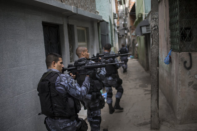Military police officers patrol in the Roquette Pinto shantytown, part of the Mare slum complex in Rio de Janeiro, Brazil, Wednesday, April 1, 2015. (Photo by Felipe Dana/AP Photo)