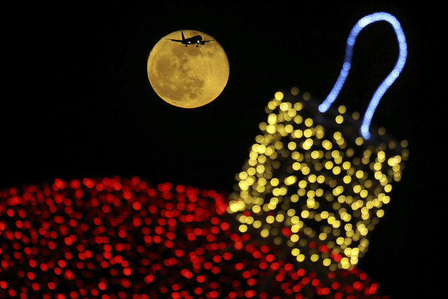 The moon shines behind a decorated with an illuminated Christmas ornament as an aircraft prepares for landing at the airport in southern coastal city of Larnaca In the eastern Mediterranean island of Cyprus, Sunday, December 23, 2018. (Photo by Petros Karadjias/AP Photo)
