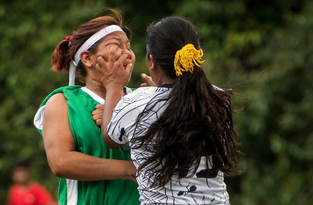 Female indigenous players vie for the ball during the final match of Peladao, the amateur football tournament, in Manaus, Amazonas state, Brazil, on November 24, 2013. Peladao is known as the biggest amateur football tournament in the world, with more than 1000 teams competing in various categories since 1973. The indigenous category was created in 2005 and eight teams participated this year. (Photo by Yasuyoshi Chiba/AFP Photo)