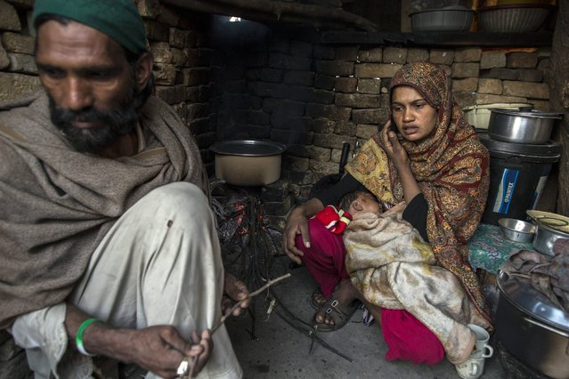 A woman talks on a mobile phone while sitting with her husband in her kitchen at a slum in Islamabad March 12, 2015. (Photo by Zohra Bensemra/Reuters)