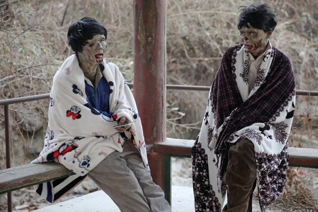 Actors wrapped in blankets react at the set of the post-apocalyptic movie Zombie Era at an abandoned factory complex in Langfang, Hebei province, China December 16, 2016. (Photo by Damir Sagolj/Reuters)
