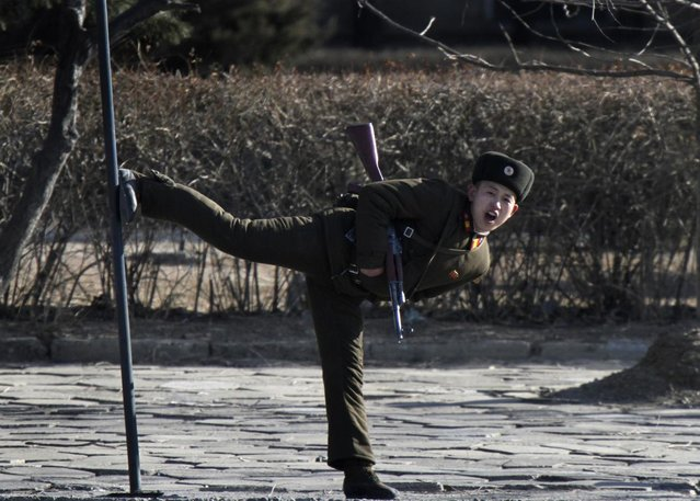 A North Korean soldier kicks a pole along the bank of Yalu River near the North Korean town of Sinuiju, opposite the Chinese border city of Dandong, February 4, 2014. (Photo by Jacky Chen/Reuters)
