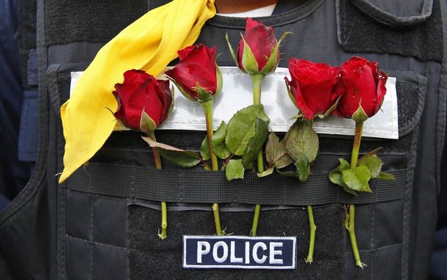 Roses offered by anti-government protesters decorate a Thai policeman's bulletproof vest outside city police headquarters, in Bangkok, Thailand Tuesday, December 3, 2013. (Photo by Manish Swarup/AP Photo)