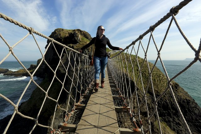 A tourist makes her way across Carrick-a-Rede Rope Bridge on the Causeway coast, north of Belfast April 8, 2015. (Photo by Cathal McNaughton/Reuters)