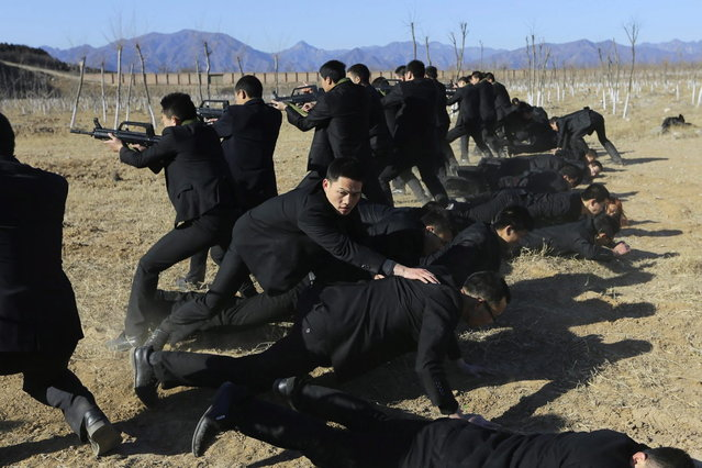 Students holding replica 95 semi-automatic rifles practice protecting their employers at a shooting training field managed by the military during Tianjiao Special Guard/Security Consultant training on the outskirts of Beijing December 14, 2013. (Photo by Jason Lee/Reuters)