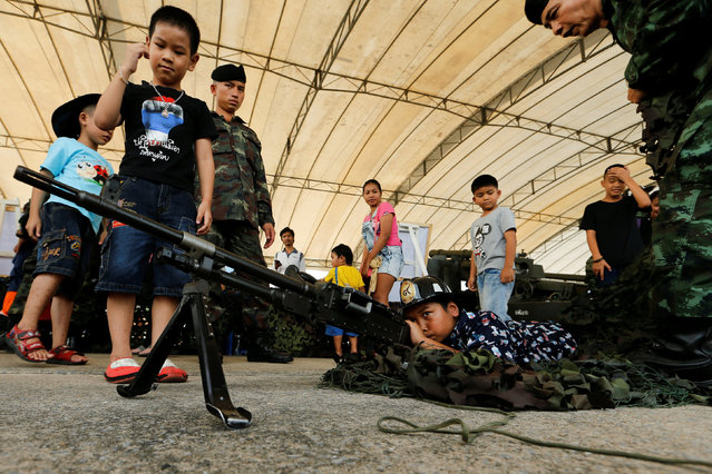 Children play with a weapon to pose for a picture during Children's Day celebration at a military facility in Bangkok, Thailand January 14, 2017. (Photo by Jorge Silva/Reuters)