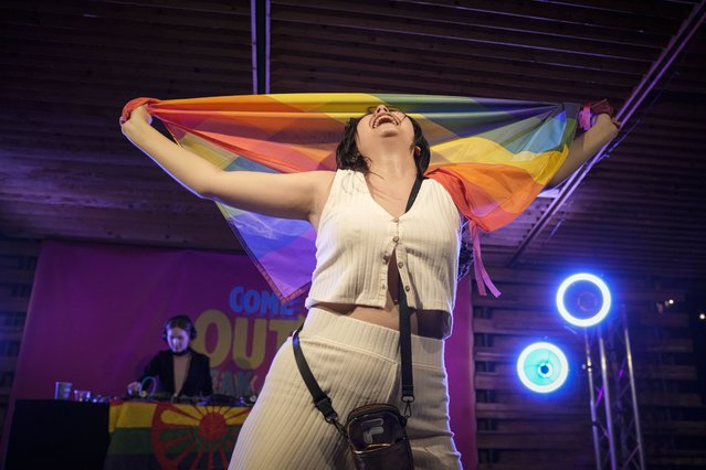 A spectator dances holding a rainbow flag at Pride Park, a venue for artistic shows ahead the Pride 2021 in Bucharest, Romania, Thursday, August 12, 2021. (Photo by Vadim Ghirda/AP Photo)