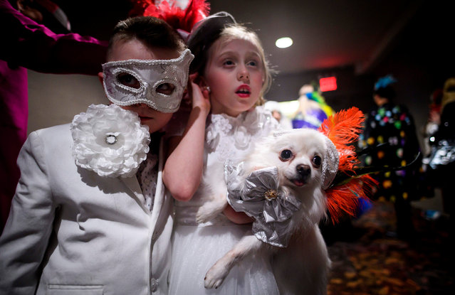 Two children hold their dog, dressed up for a show, backstage at the 16th annual New York Pet Fashion Show on February 7, 2019 in New York City. (Photo by Johannes Eisele/AFP Photo)
