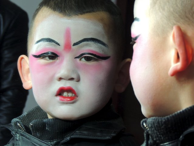 A boy wearing make-up for a traditional folk art show is seen reflected in a mirror in Xining, Qinghai Province, China, February 20, 2016. (Photo by Reuters/Stringer)
