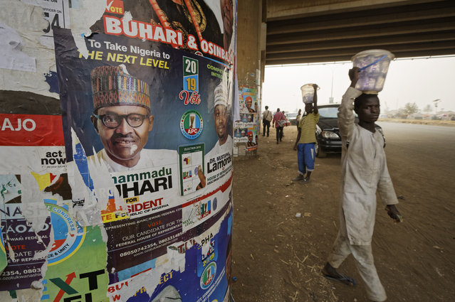 The face of incumbent President Muhammadu Buhari is seen on a campaign poster fixed to the pillars of a highway bridge near Nyanya, on the eastern outskirts of the capital Abuja, Nigeria Tuesday, February 12, 2019. (Photo by Ben Curtis/AP Photo)