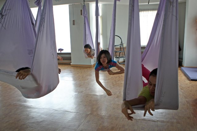 Some women sleep on the hammocks during the Anti-Gravity yoga class at Svarga e-Motion Sanctuary at Dharmawangsa Square, Jakarta, Saturday, April 18, 2015. (Photo by Jurnasyanto Sukarno/JG Photo)