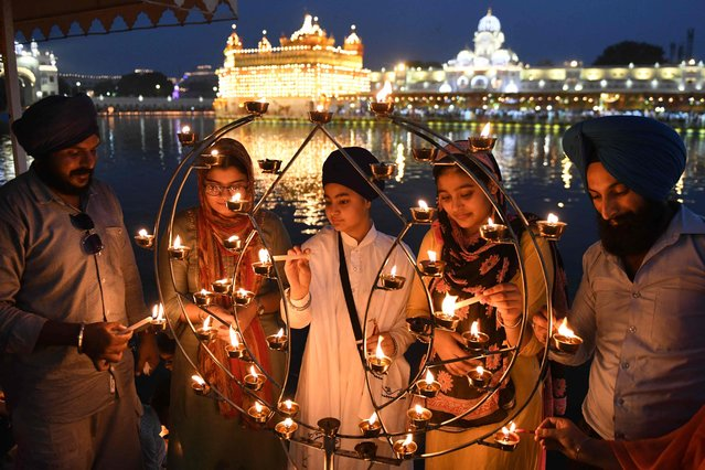 Sikh devotees light candles on the occasion of the 417th anniversary of the installation of the Guru Granth Sahib, at the illuminated Golden Temple in Amritsar on September 7, 2021. (Photo by NNarinder Nanu/AFP Photo)
