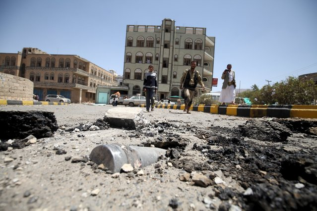 People look at an artillery shell in the ground along a damaged street, caused by an April 20 air strike that hit a nearby army weapons depot, in Sanaa April 21, 2015. (Photo by Mohamed al-Sayaghi/Reuters)