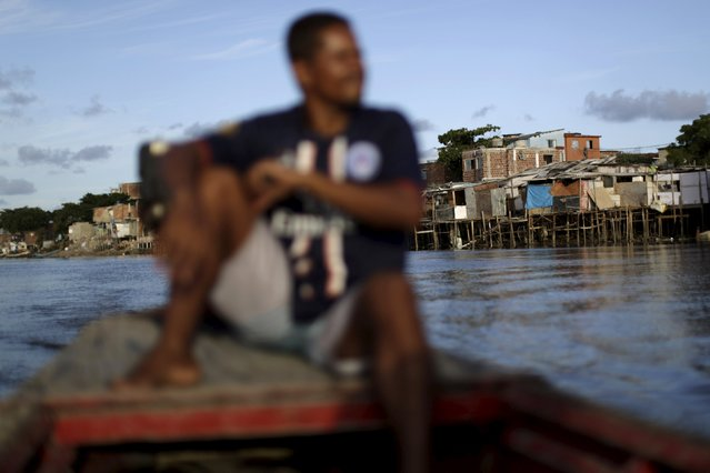 "Ivanildo sits in his boat near stilt houses at a lake dwelling also known as palafitte or ""Palafito"" in Recife, Brazil, March 1, 2016. (Photo by Ueslei Marcelino/Reuters)"
