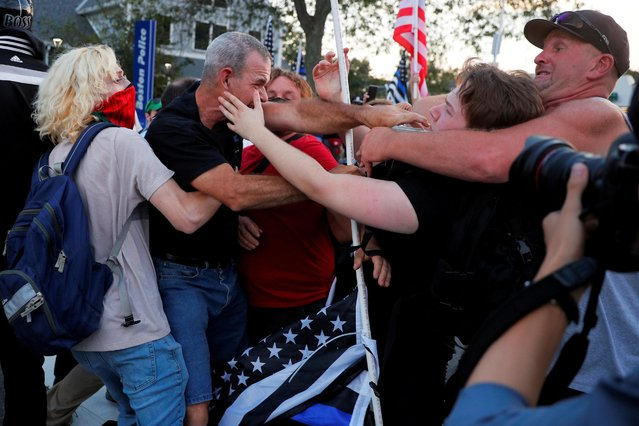 """A group holding a """"Back the Blue"""" demonstration scuffles with counter-protestors outside a police station in the West Roxbury neighborhood of Boston, Massachusetts, U.S., September 15, 2021. (Photo by Brian Snyder/Reuters)"""