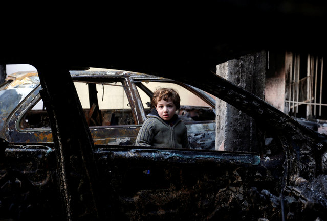 A child is seen at a house which was burned by Islamic State militants before they fled the area, in the Arabi neighborhood in Mosul, Iraq January 26, 2017. (Photo by Muhammad Hamed/Reuters)