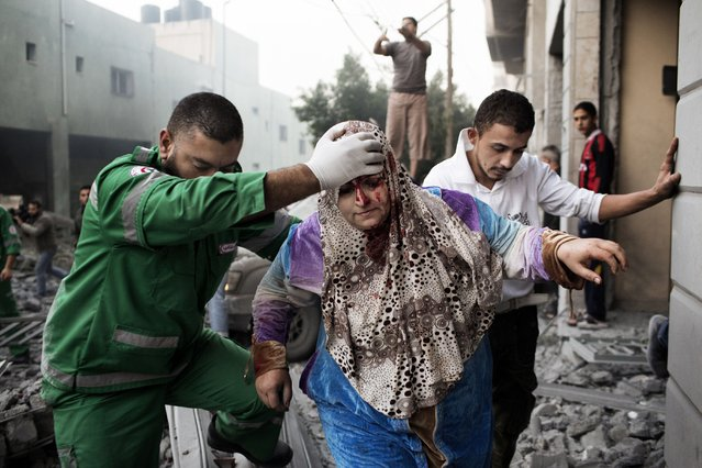 A Palestinian woman is helped by a paramedic out of her building, damaged during an Israeli air raid on a nearby sporting centre in Gaza City November 19, 2012. (Photo by Marco Longari/AFP Photo)