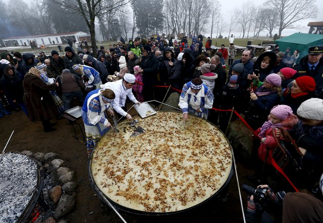 Employees cut fried dranik, a potato pancake that is the national dish of Belarus, to entertain visitors in the Sula History Park near the village of Sula, Belarus March 7, 2016. (Photo by Vasily Fedosenko/Reuters)