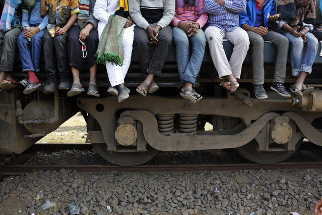 Bangladeshi Muslims board overcrowded trains to return home after attending three-day Islamic Congregation on the banks of the River Turag in Tongi, 20 kilometers (13 miles) north of the capital Dhaka, Bangladesh, Sunday, January 26, 2014. (Photo by A. M. Ahad/AP Photo)
