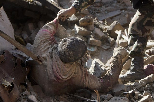 Members of Nepalese army rescue a dead body from inside a building that collapsed in Saturday's earthquake, in Bhaktapur, on the outskirts of Kathmandu, Nepal, Monday, April 27, 2015. (Photo by Niranjan Shrestha/AP Photo)