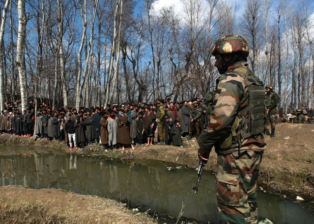 An Indian soldier stands guard as people look at the wreckage (unseen) of Indian Air Force's helicopter after it crashed in Budgam district in Kashmir February 27, 2019. (Photo by Danish Ismail/Reuters)