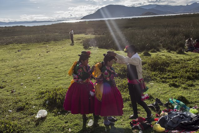 In this January 29, 2017 photo, dancers get ready near Lake Titicaca prior to their performance at Virgin of Candelaria celebrations in Puno, Peru. The festivities start this week. The Feast in honor of Virgin of Candelaria, patron of the city of Puno, is made in the first fortnight of February each year, and represents the largest and most important cultural event, musical and dancing by Peru, and one of the three most significant in South America along with Carnival in Rio de Janeiro and the Carnaval de Oruro, in the amount of symbols and artistic and cultural manifestations of the cultures themselves Quechua, Aymara and mixed by Highlands Andean and the volume of people directly and indirectly involved in its realization. (Photo by Rodrigo Abd/AP Photo)