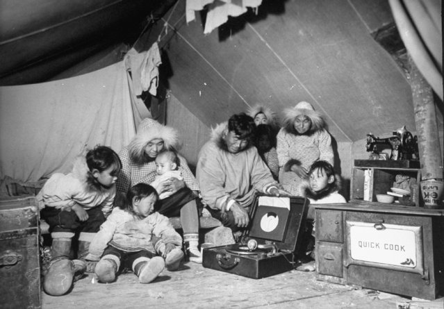Eskimo family admiring their modern conveniences, a victrola (C), a sewing machine & a stove (R) as they commune in their tent, October 1937. (Photo by Margaret Bourke-White/The LIFE Picture Collection/Getty Images)